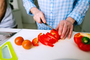 Hands of unrecognizable senior woman cutting red pepper.