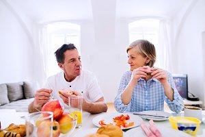 Senior man and woman having breakfast. Sunny morning.