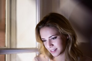 Blond woman sitting on window sill with smart phone