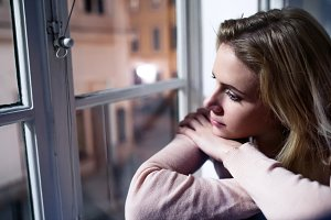 Woman sitting on window sill, looking out of window