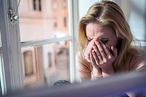 Woman sitting on windowsill, looking out of window, crying