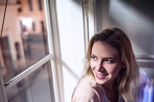 Woman sitting on windowsill, looking out of window, smiling