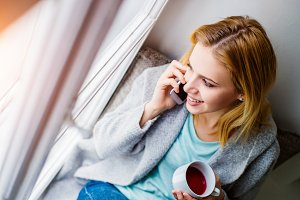 Woman on window sill with smartphone making phone call