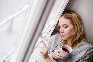 Woman on window sill holding a cup of tea
