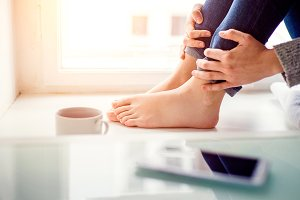 Feet of unrecognizable woman sitting on window sill