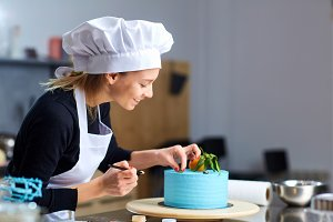 A confectioner woman decoration a cake  in kitchen.
