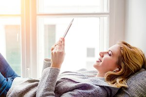 Woman lying on window sill with smartphone, listening music