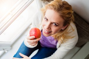 Woman on window sill holding fresh red apple