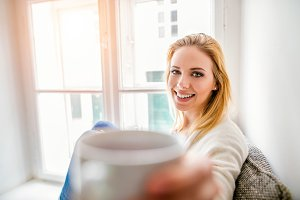 Woman on window sill holding a cup of coffee