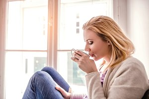 Woman on window sill holding a tea cup, drinking