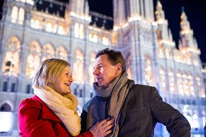 Senior couple walking in night city. Winter, Historical building