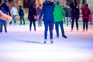People ice skating at night in Vienna, Austria. Winter.