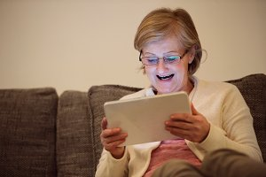 Senior woman with tablet sitting on couch in living room