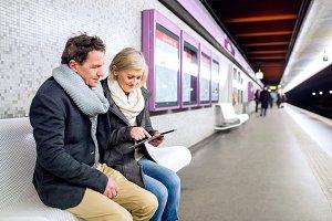Senior couple sitting at the underground platform, waiting