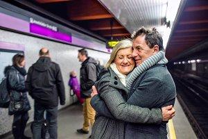 Senior couple standing at the underground platform, hugging, wai