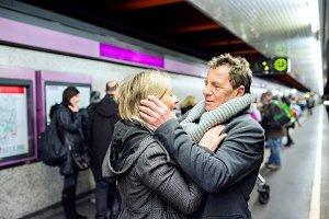 Senior couple standing at the underground platform, hugging