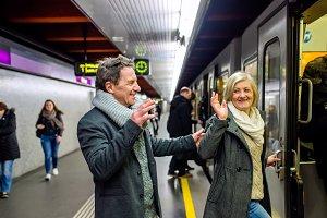 Senior couple standing at the underground platform, entering tra