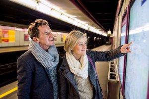 Senior couple standing at the underground platform, waiting