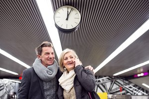 Senior couple standing at the underground platform, calling