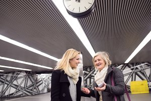 Two beautiful women standing at the underground platform, talkin