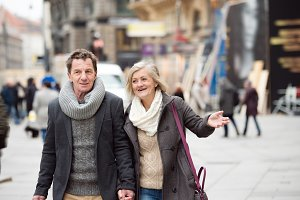 Senior couple on a walk in city centre. Winter