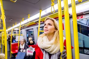 Beautiful young woman in red coat in subway train