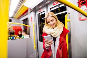 Beautiful young woman with smart phone in subway train