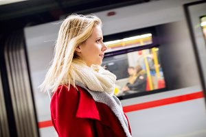 Beautiful young woman at the underground platform, waiting