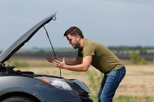 Picture of frustrated man next to broken car with open hood