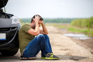 Picture of frustrated man sitting next to broken car with open hood