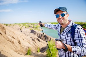 Image of cheerful tourist man with backpack stretching forward with sticks for walking on hill