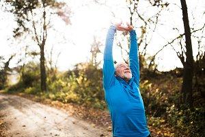 Senior runner doing stretching in sunny autumn nature.