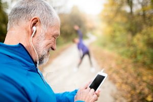 Senior runners in nature, stretching. Man with smartphone with e