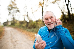 Senior runner in nature with smart phone with earphones.