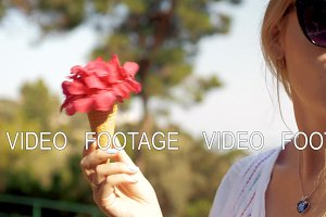Coquettish girl with red summer bouquet in waffle cone