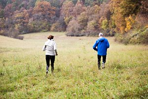 Senior couple running in sunny autumn nature, rear view