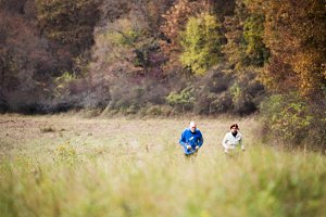 Beautiful senior couple running outside in sunny autumn nature