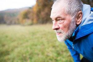 Senior runner in nature. Man resting. Close up.