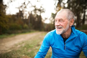 Senior runner in nature. Man resting, smiling. Close up.