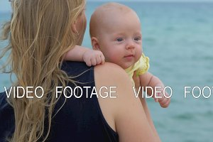 Mum with baby daughter enjoying sea and breeze