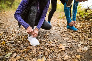 Unrecognizable runners in nature, tying shoelaces. Man with smar