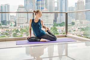 Young woman is practicing yoga in the morning on her balcony with a panoramic view of the city and skyscrapers