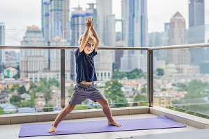 Happy little boy is practicing yoga on his balcony with a panoramic view of the big city