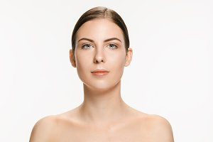 Beautiful face of young adult woman with clean fresh skin isolated on white