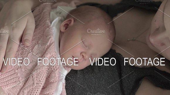 Mother Stroking Beloved Newborn Daughter Sleeping On Her Chest