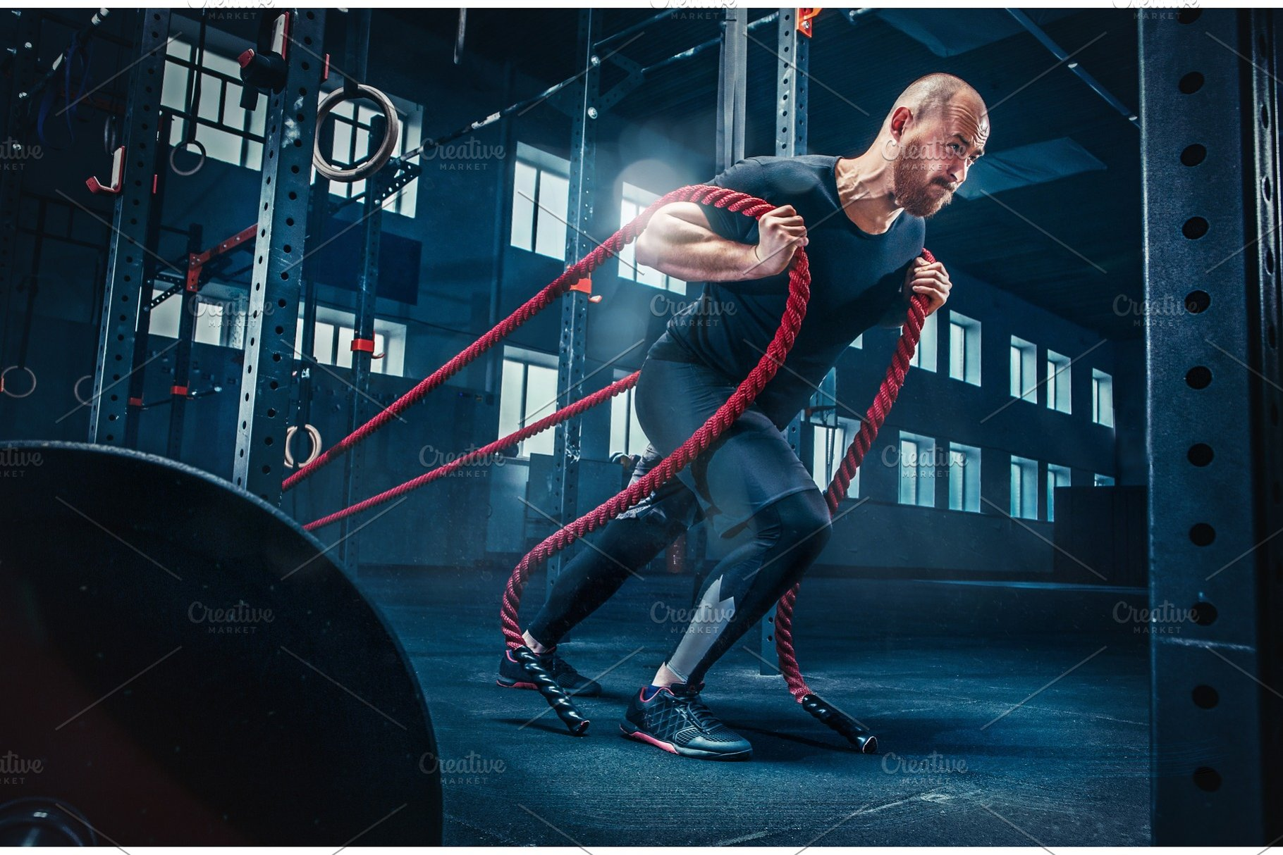 Men with battle rope battle ropes exercise in the fitness gym