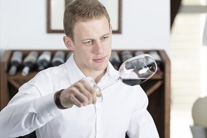man analyzing a red wine glass