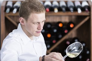man analyzing a white wine glass