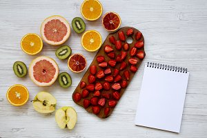 Fresh ripe fruits and notebook