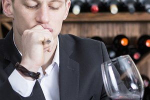 man evaluating a red wine